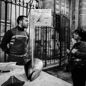 A fishmonger chats with a client at the historical street market of Capo in Palermo. March 2009